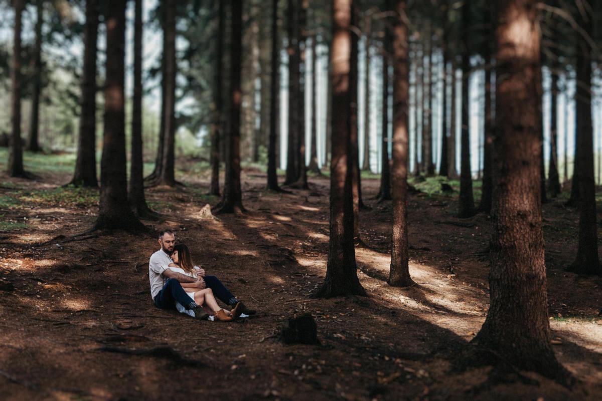 Narzeczeni siedza w klimatycznym lesie