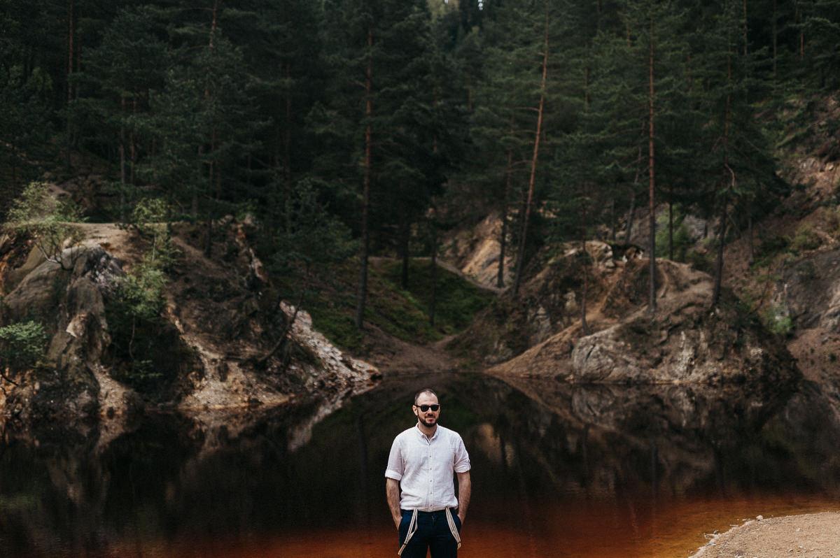 Pan mlody stojacy na brzegu jeziora w gorach