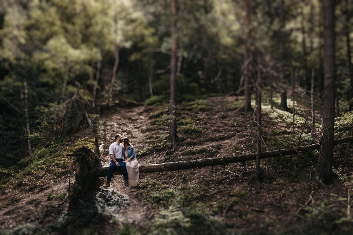 Przyszla boho para mloda siedzi na przewroconym drzewie w gorach