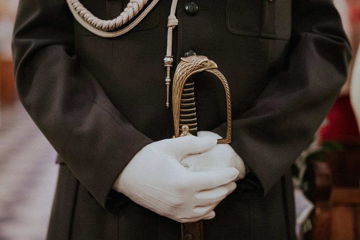 Orszak wojskowy z szabla w białych rekawiczkach