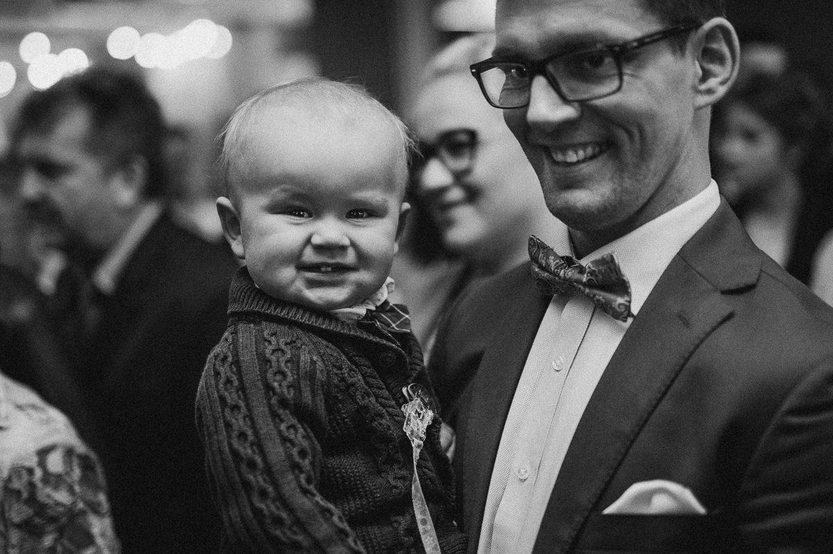 Usmiechniete dziecko trzymane przez ojca na rekach