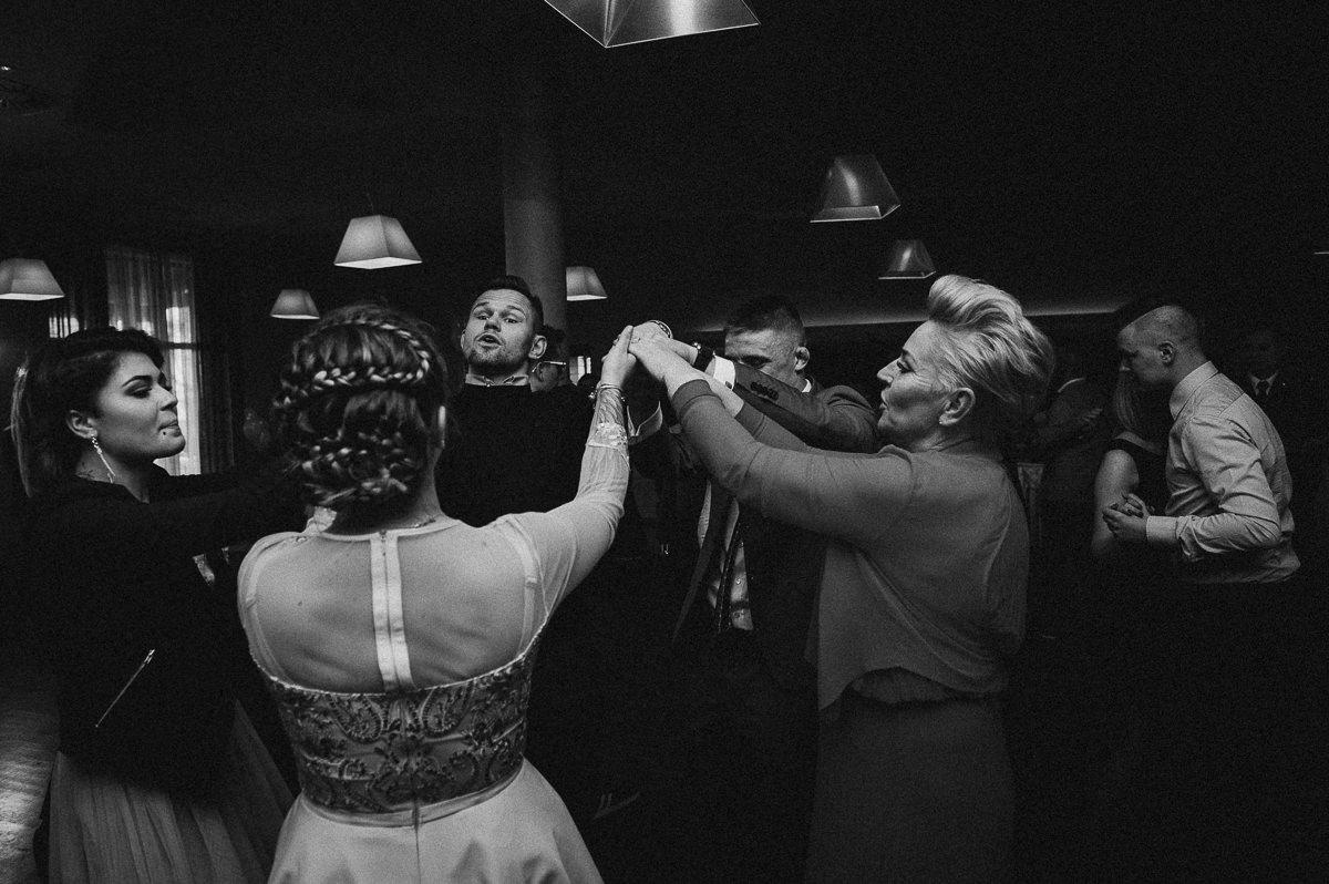Ludzie tancza w kolku trzymajac sie za dlonie