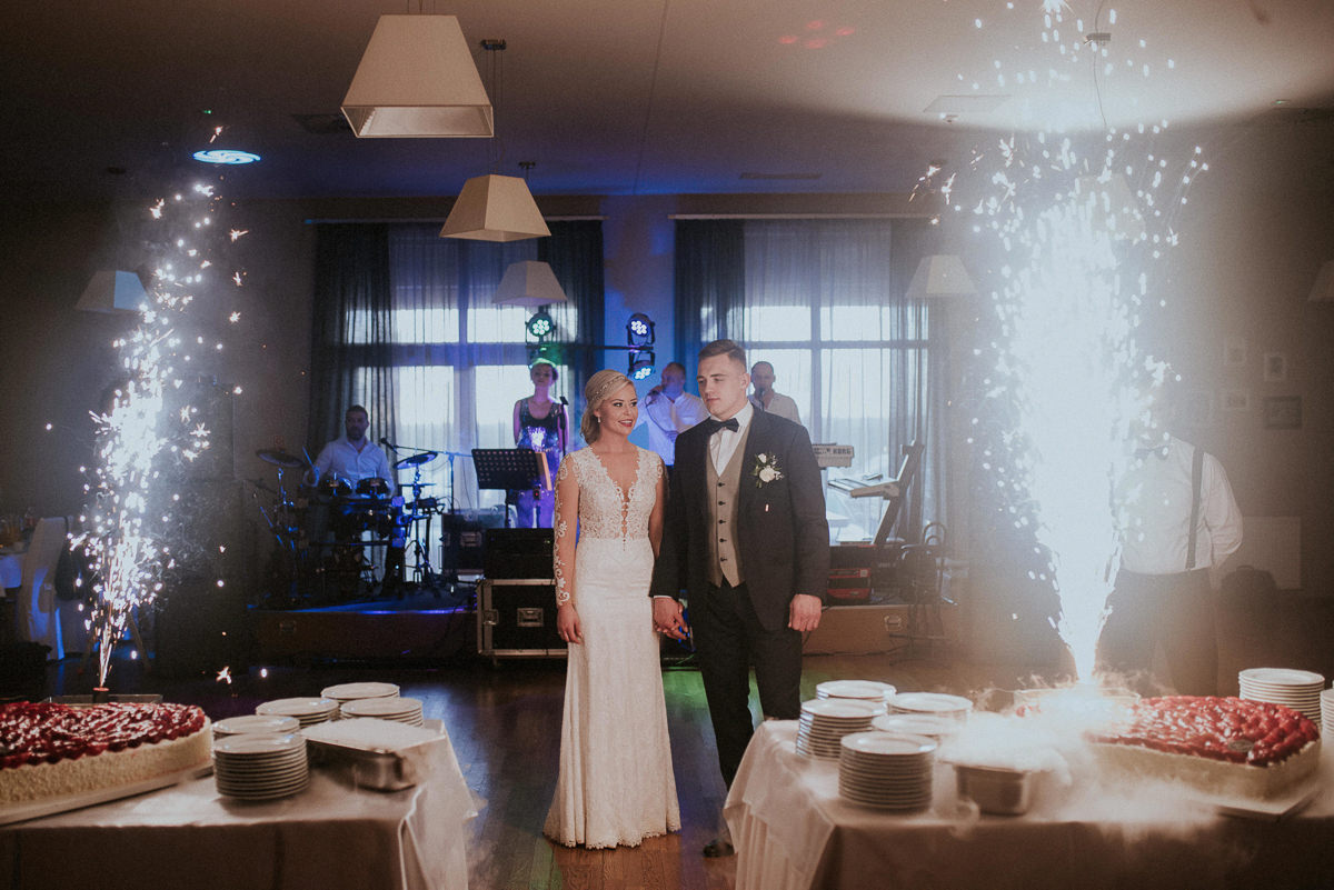 Para mloda stoi przed tortem weselnym i oswietlaja ich race
