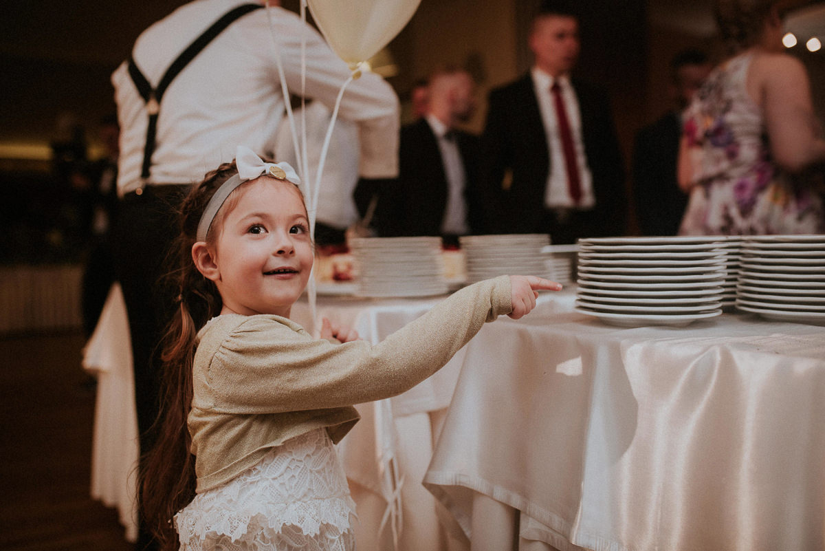 Dziewczynka pokazuje palcem na tort slubny