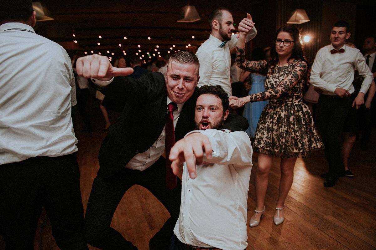 Goscie tancza i pokazuja palcem na fotografa slubnego