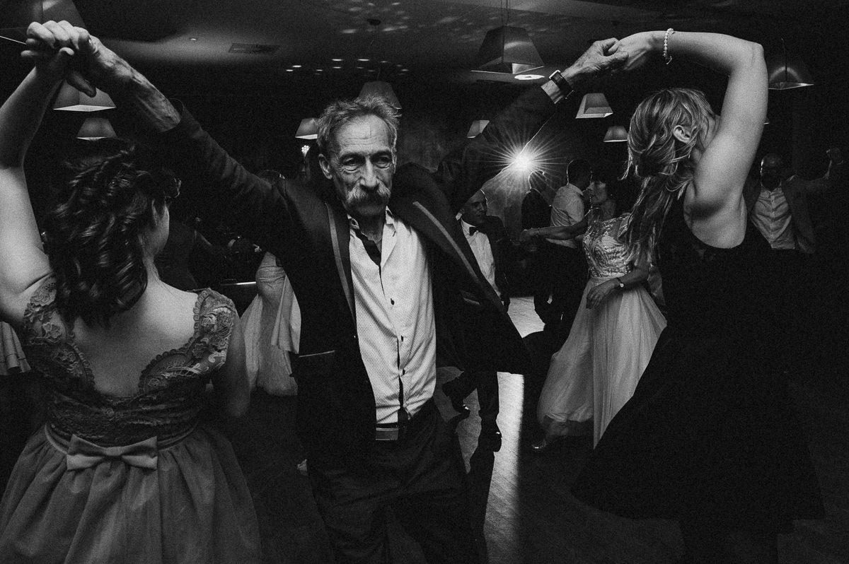 Dziadek obraca dwie dziewczyny podczas tancow