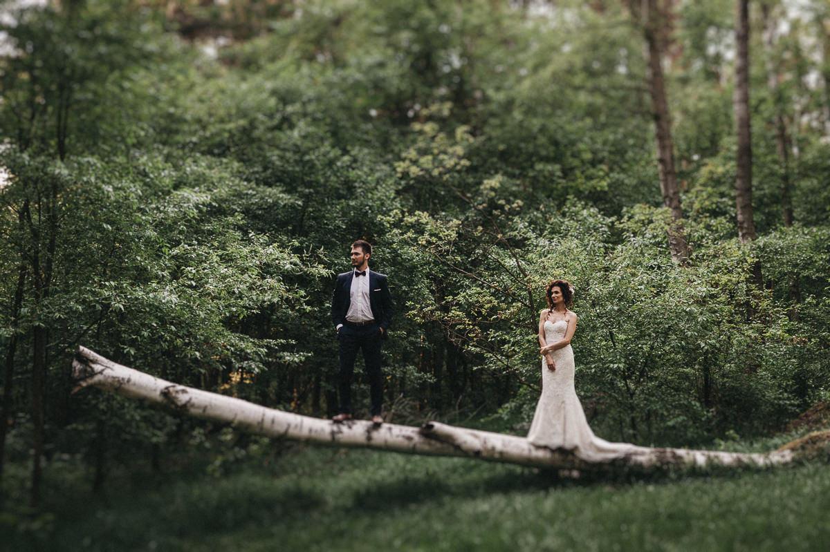 Para mloda stoi na przewroconym drzewie w lesie