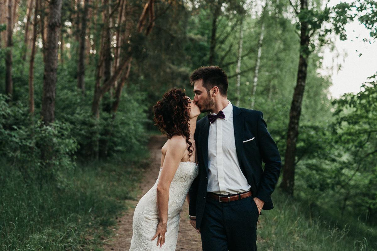 Romantyczny pocalunek pary mlodej w lesie
