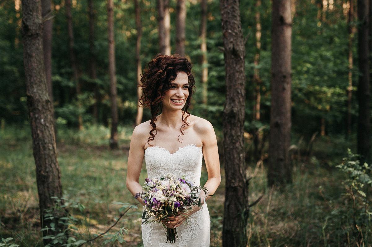 Portret panny mlodej z bukietem slubnym w lesie
