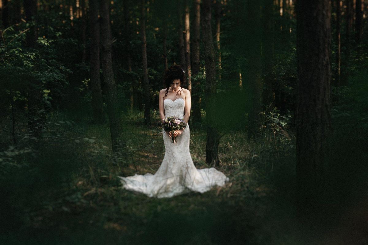 Panna mloda stoi posrodku lasu
