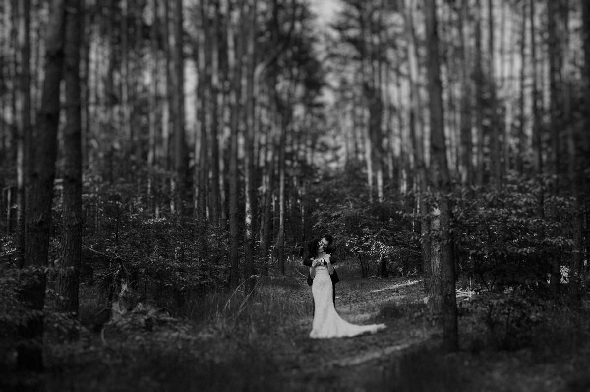 Para mloda przytula sie do siebie w srodku lasu
