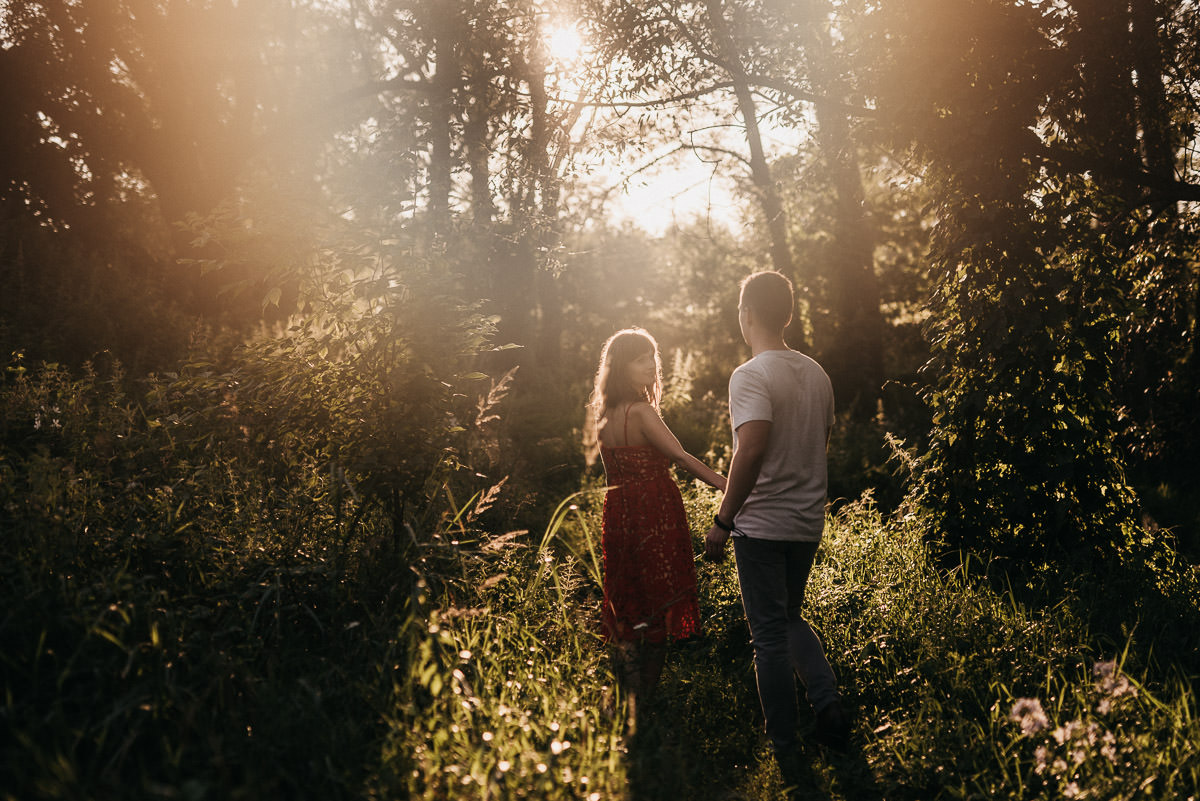 Zakochana para spaceruje po lesie w promieniach slonca